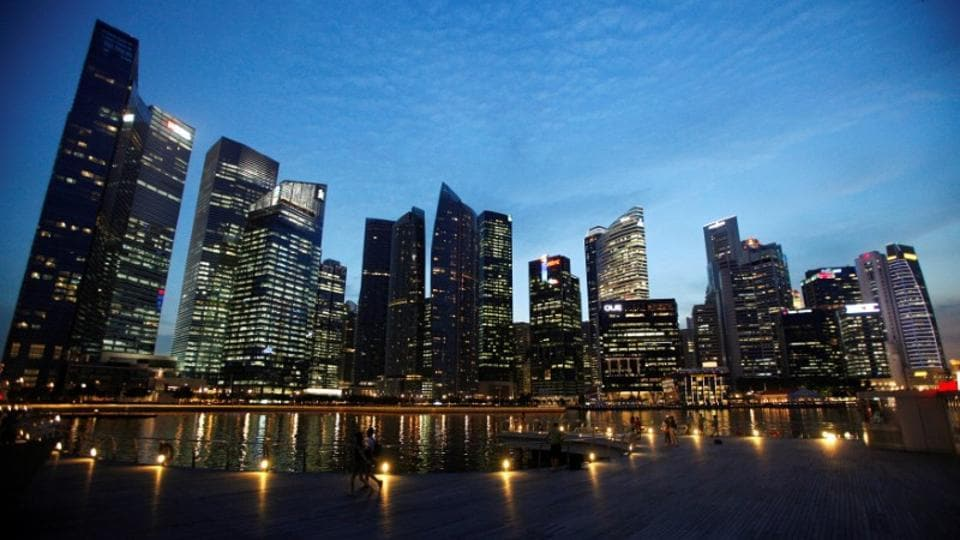 People walk past the skyline of Marina Bay central business district in Singapore.