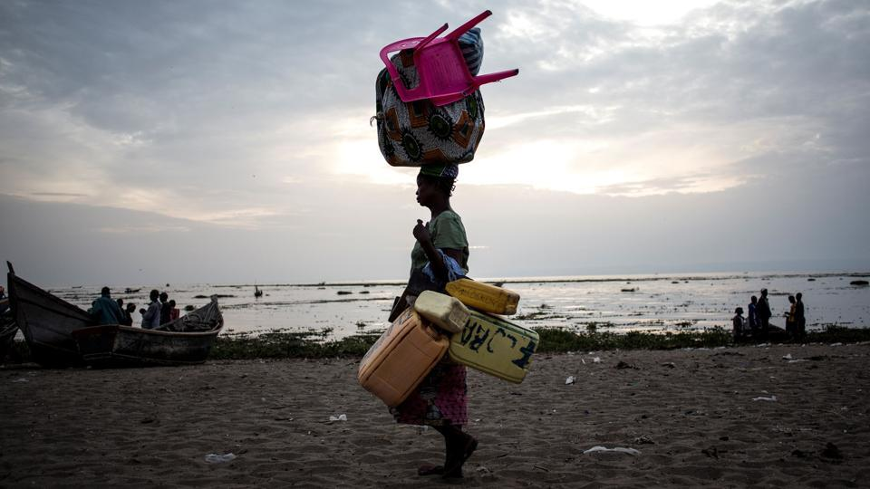 A displaced Congolese woman walks with her belongings along the shore line of Lake Albert after spending the night out by the lake for safety. Congo is also dealing with its worst cholera outbreak in decades, which killed more than 1,000 people last year. As of last month, cases in the capital Kinshasa were declining but the situation remained alarming. (John Wessels / AFP)