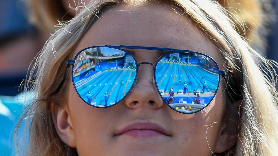 The pool is reflected in the glasses of a spectator during a swimming event at the Optus Aquatic Centre on April 7, 2018. (Manan Vatsyayna / AFP)