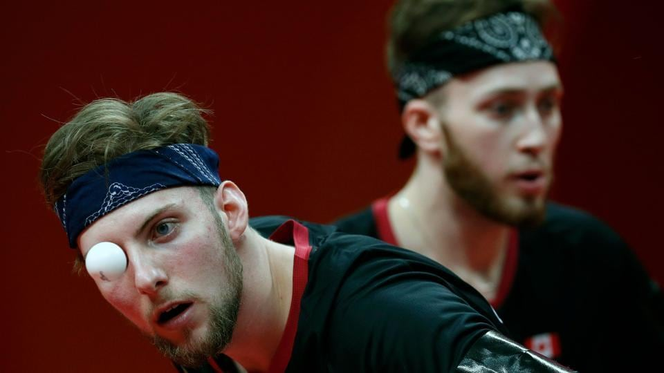 Canada's Marko Medjugoracz (L) serves alongside partner Antoine Bernadet during the men's team quarter-final table tennis match against Singapore at the Oxenford Studios venue on April 7, 2018. (Adrian Dennis / AFP)