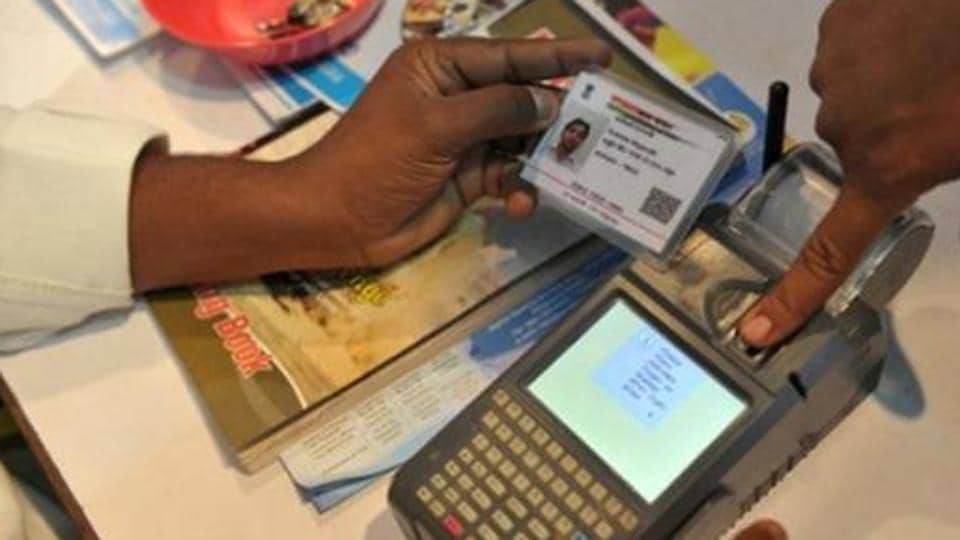 An Indian visitor gives a thumb impression to withdraw money from his bank account with his Aadhaar or Unique Identification (UID) card.