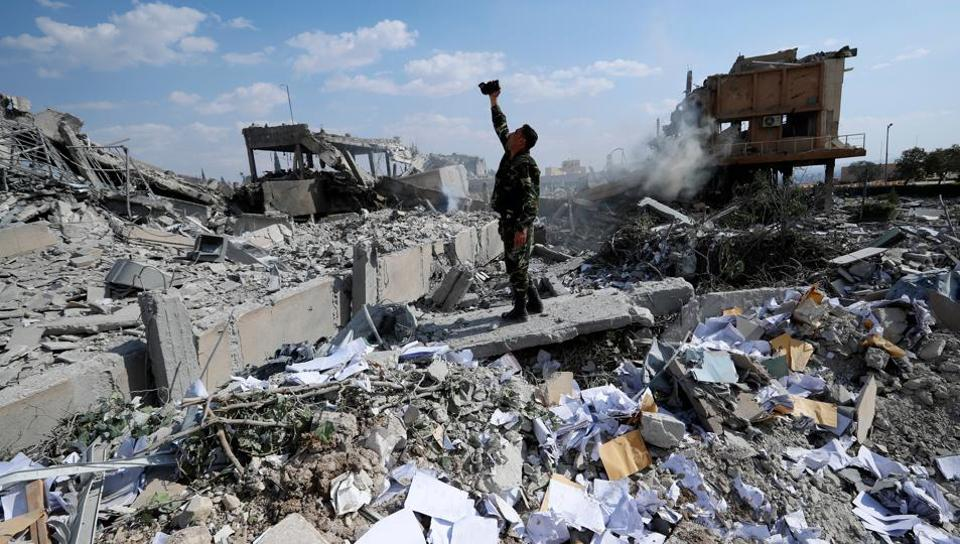 A Syrian soldier on Saturday films the damage of the Syrian Scientific Research Centre which was attacked by US, British and French military strikes to punish President Bashar Assad for suspected chemical attack against civilians.