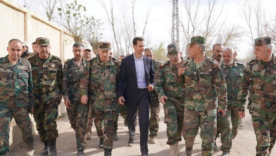 Syrian President Bashar al-Assad walks with Syrian army soldiers in eastern Ghouta, Syria, March 18, 2018.
