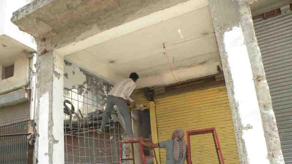 People vacate encroached land in the main market in Rudrapur on Monday.