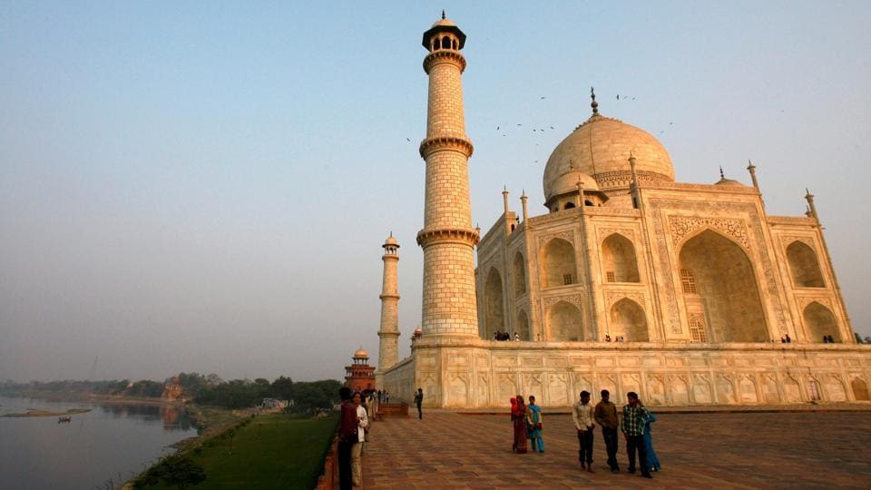 Tourists Walk In Front Of The Historic Taj Mahal In Agra.