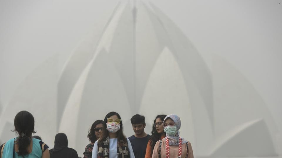 Tourists wear masks as they visit Lotus Temple on a smoggy morning, in New Delhi, on November 7, 2017.