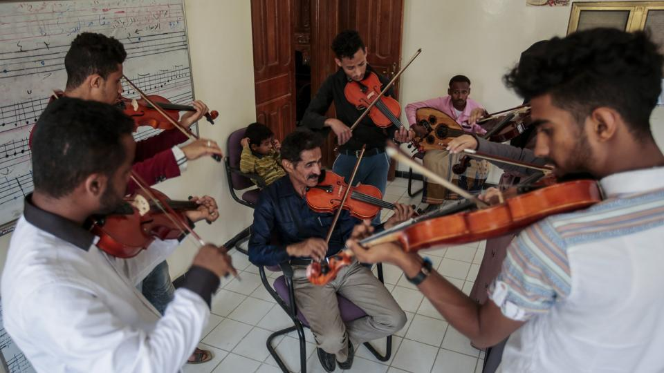 Abdullah El-Deb'y (C), instructs his students during a music class at the Cultural Centre. El-Deb'y offers free lessons to students eager to escape — at least psychologically — for a time the suffering caused by the war and is seeking to form a national orchestra amid the bombing comprised of young Yemenis. (Hani Mohammed / AP)