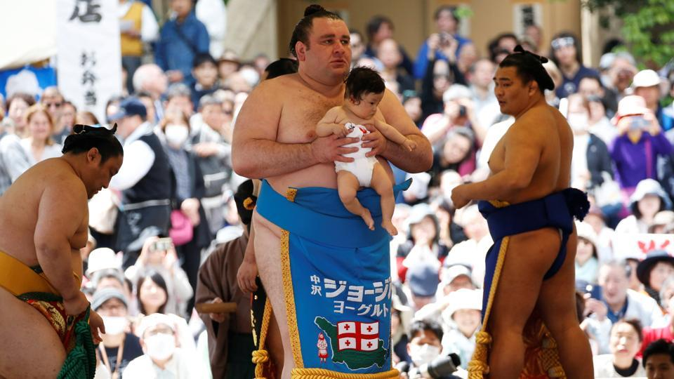 Georgian sumo wrestler Gagamaru (C) carries a baby in the ring during the tournament. Many fans leaving the shrine on Monday believed that sumo wrestling should be more inclusive, particularly with the next Summer Olympics 2020 taking place in Tokyo. (Toru Hanai / REUTERS)