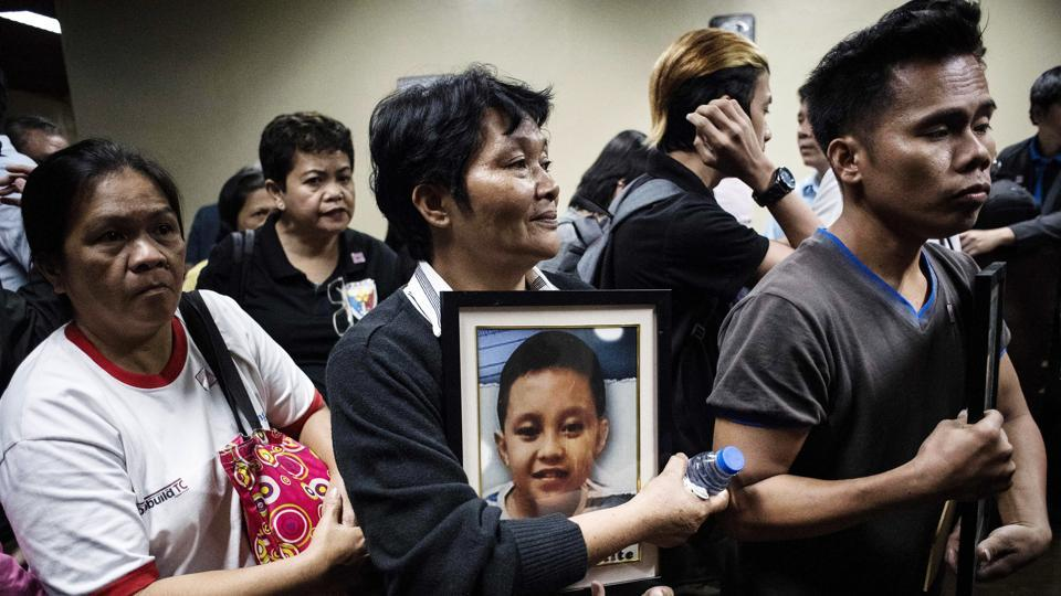 "Melinda Colite (C) shook with rage, holding a picture of her grandson Zandro Colite, who she says died after getting injected with the anti-dengue fever vaccine Dengvaxia, during a Senate investigation about the vaccine in Manila. ""It could not have been anything else. He started complaining of frequent body aches after his third injection,"" Colite, 55, said of her 12-year-old grandson Zandro. (Noel Celis / AFP)"