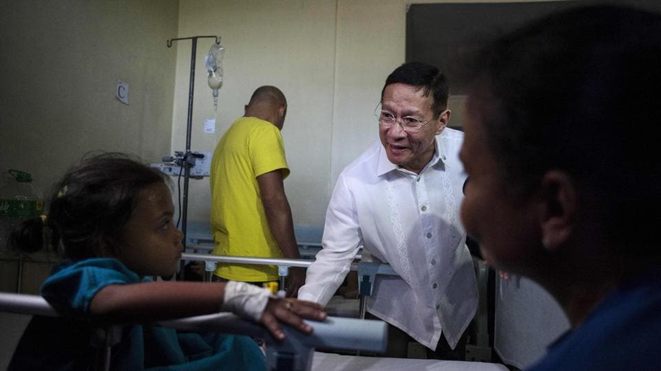 "Philippines' Department of Health Secretary Francisco Duque talks to a dengue patient who hasn't taken the vaccine. As of last week 65 deaths have been reported, the health department says. Different branches of the government have disagree openly about the vaccine, adding to public confusion. ""We cannot conclude at this point that Dengvaxia directly caused the deaths,"" Duque told lawmakers in February. (Noel Celis / AFP)"