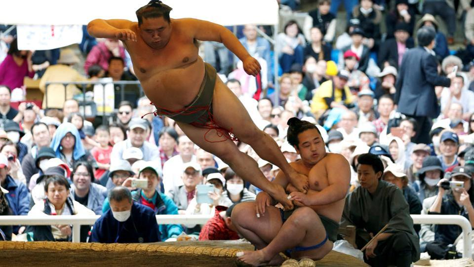 A sumo wrestler kicks his opponent out of the ring during a show fight at the ceremonial Spring Festival sumo tournament held in Tokyo, Japan on Monday. Hardcore sumo fanatics and tourists alike flocked to the event held at the controversial Yasukuni war shrine, seen by many in Asia as a symbol of Japan's past militarism. (Toru Hanai / REUTERS)