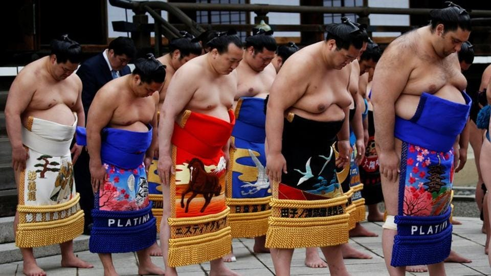 Sumo wrestlers pray at the Yasukuni  shrine. Fans, fresh from seeing their heroes up close in the Tokyo sunshine, hoped that this particular ceremony leads to a scandal-free year as sumo looks to rebuild a tarnished reputation. (Toru Hanai / REUTERS)