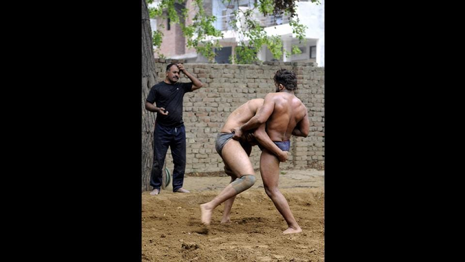 Surendra Singh Yadav (L), an army veteran, trains wrestlers in the loose soil mixed with henna, mustard oil and turmeric in Sarfabad. Sukhbir Singh (not pictured), an army veteran and former wrestler who also runs an 'akhara' in the village believes once wrestlers are past their prime, it is the duty of society to ensure they don't lose dignity in search of livelihood. (Sunil Ghosh / HT Photo)