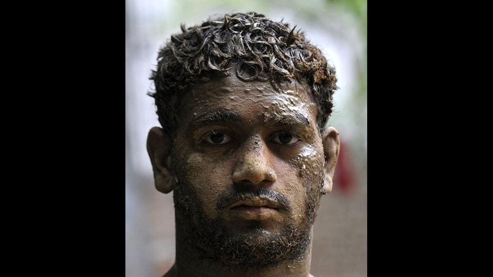 A young wrestler caked with soil post a training session. A regular diet for any wrestler includes huge quantities of almonds, 1.5 litres milk, fruits, juice and other protein nutrients running up to Rs. 1000 a day. Although the wrestlers here train for free, the cost of such diets piles up, making it difficult for even a few to take up wrestling professionally. (Sunil Ghosh / HT Photo)