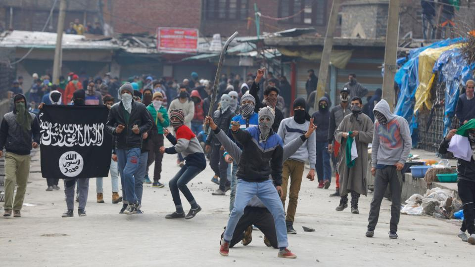 Kashmiri protesters wave an ISIS flag and throw stones towards security forces during clashes in Srinagar on February 17, 2017.