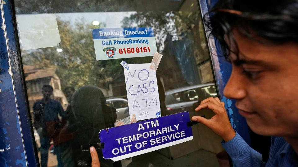 A security guard puts a notice outside an ATM in Mumbai, India.