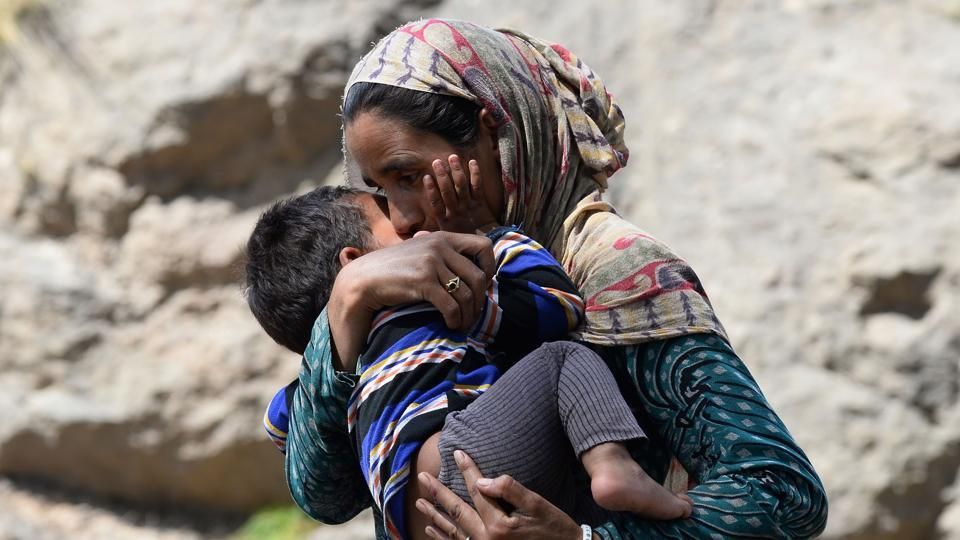A woman belonging to the Bakarwal nomadic community holds her son at a temporary camp near Udhampur in Jammu. The Muslim nomads who lead their goats, cows and horses up and down the Kashmir hills have speeded up their annual migration out of Jammu due to rising tensions between the community after the rape and murder of an eight-year-old girl in Kathua. (Sajjad Hussain / AFP)