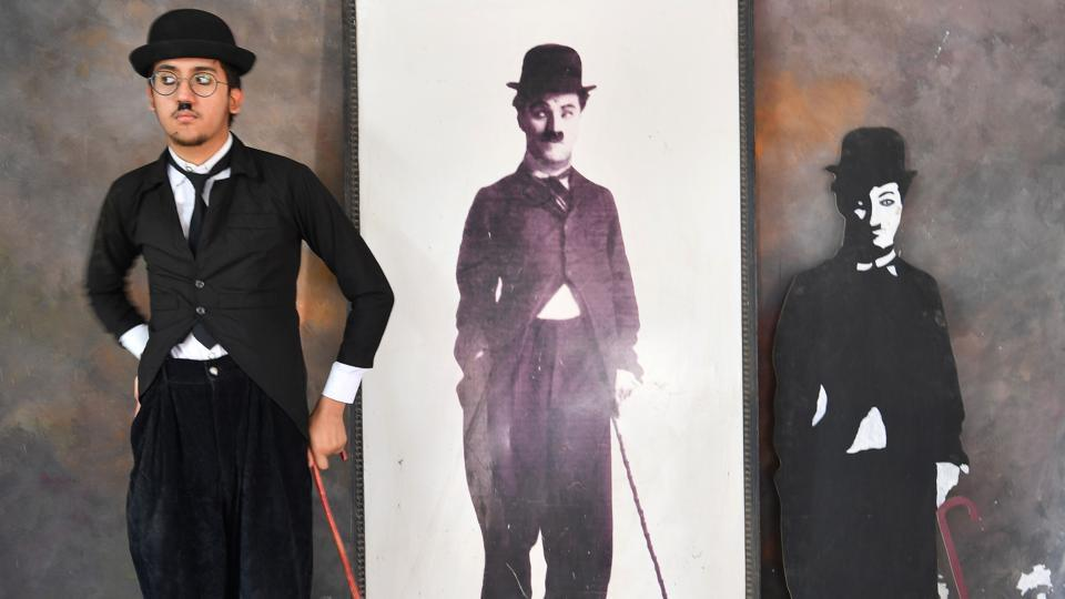 Talin Mavani, a Charlie Chaplin impersonator, checks his appearance in a mirror as he stands next to images of the legendary comedian on the occasion of his birthday in Adipur, Gujarat. Participants young and old, male and female, were members of Charlie Circle, a local fan club that has been marking Chaplin's birthday annually since 1973. (Indranil Mukherjee / AFP)