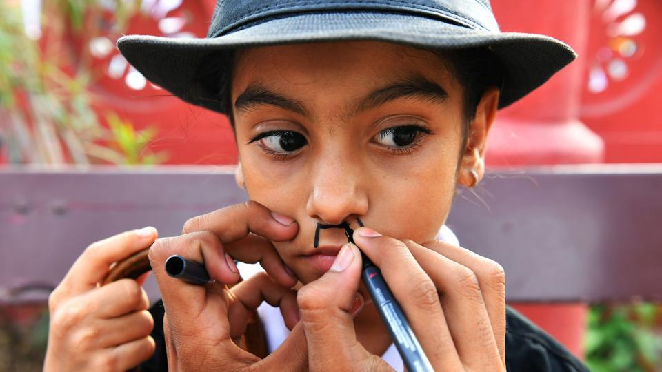 Many had used black marker pens to draw on Chaplin's trademark toothbrush moustache while others chose to stick to fake ones. (Indranil Mukherjee / AFP)