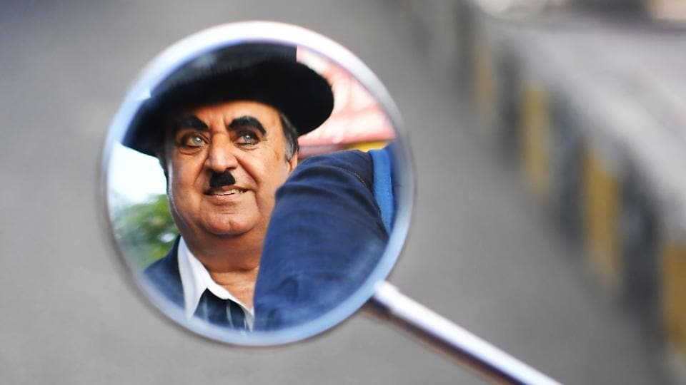 "Ashok Aswani, founder of the Charlie Circle fan club, is reflected in a mirror as his daughter Monica drives him around. He was cycling to work one day in the early '70s when he passed a theatre showing Chaplin's 1925 hit ""The Gold Rush"". He bought a ticket and went in. Immediately hooked, Aswani watched three consecutive shows, skipping work. He was fired from his job the next day. (Indranil Mukherjee / AFP)"