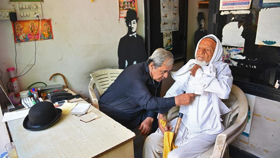 Ashok Aswani (L), an ayurvedic doctor by profession checks a patient at his dispensary in Adipur. Aswani discovered that he enjoyed copying the mannerisms of Chaplin's most famous on-screen persona 'The Tramp' and began paying homage to his new-found idol. (Indranil Mukherjee / AFP)