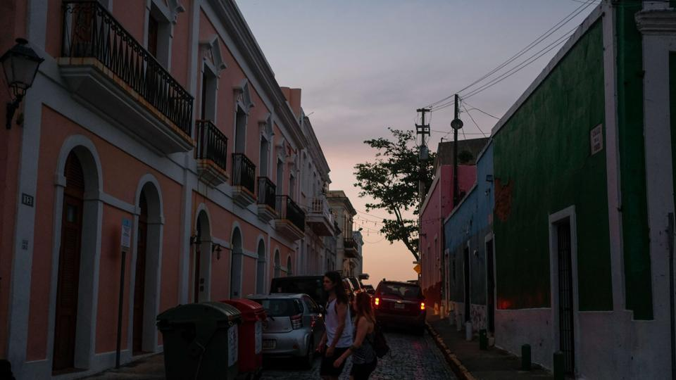 Tourists walk along San Sebastian street on Wednesday in Old San Juan, Puerto Rico as a major failure knocked out the electricity in the area.