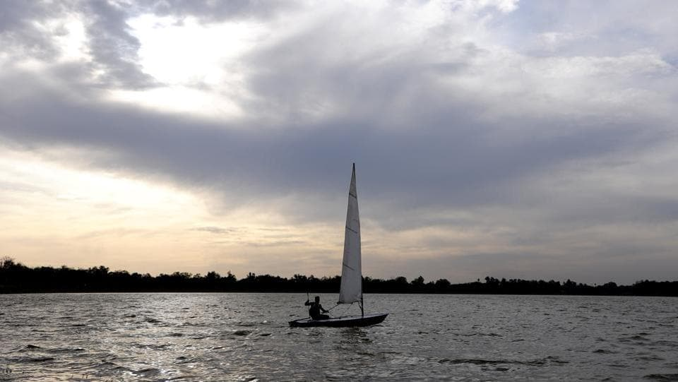 The windy weather at Sukhna Lake gave this man a chance to take his sail boat out for a ride.  (Keshav Singh/HT)