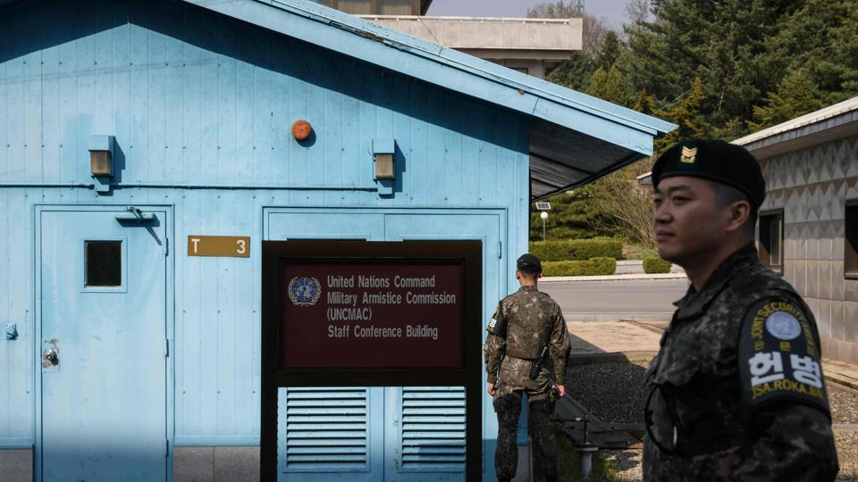 A photo taken on March 18, 2018 shows a South Korean soldier standing guard before a United Nations Command Military Armistice Commission (UNCMAC) meeting hut in the truce village of Panmunjom within the Demilitarized Zone (DMZ) separating North and South Korea.