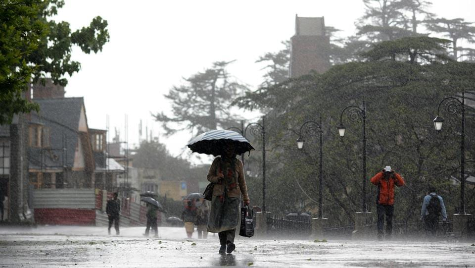 People take a stroll during the wind storm and rain at Ridge on Friday evening, in Shimla. (Deepak Sansta/HT)