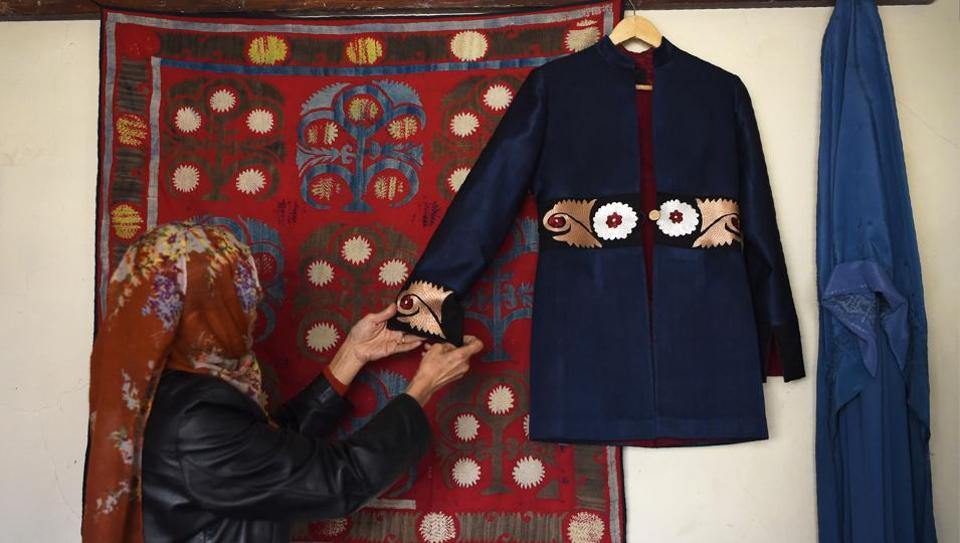 An Afghan tailor hangs an embroidered coat on the wall at Zarif Design House in Kabul. As mass produced nylon and polyester burkas made in China flood Afghanistan feeding consumer appetite for affordable, mass-produced fabric, this small but determined fashion house is fighting to preserve the traditional textiles once integral to Afghan culture. (Wakil Kohsar / AFP)