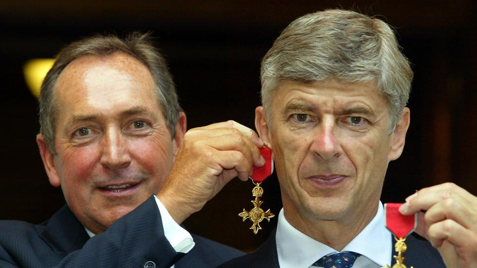 Gerard Houllier (L) holds his OBE medal as an earring on long-term friend and Arsene Wenger. (AFP)