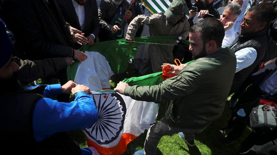 Protesters rip up India's flag after tearing it off a flagpole in Parliament Square, London.