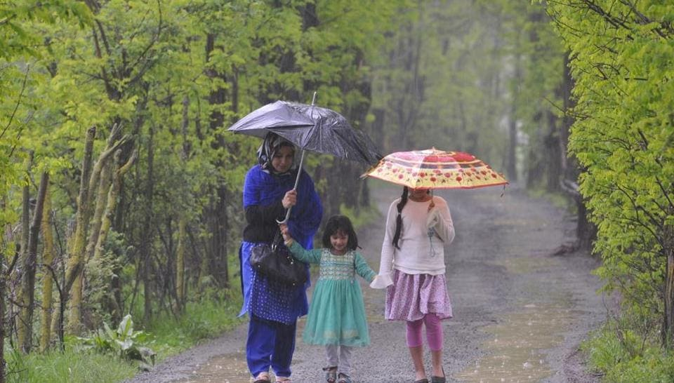 A Kashmiri woman walks along with her children as it rains in Srinagar on Friday. The minimum temperature was 8.6 degrees Celsius in Srinagar. (Waseem Andrabi /HT)