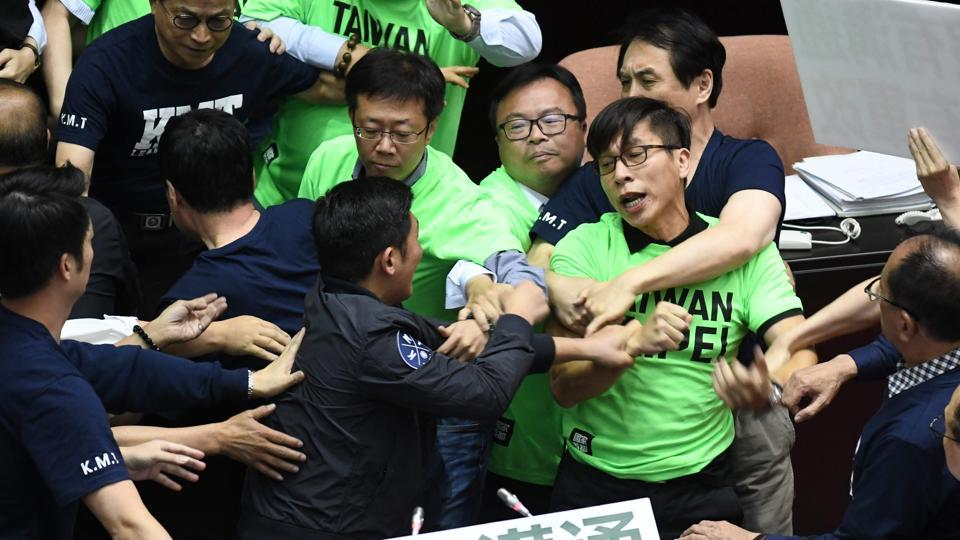 Lawmakers from the ruling Democratic Progressive Party (DPP) and the Kuomintang (KMT) scuffle during a protest at the Parliament in Taipei on April 20, 2018.