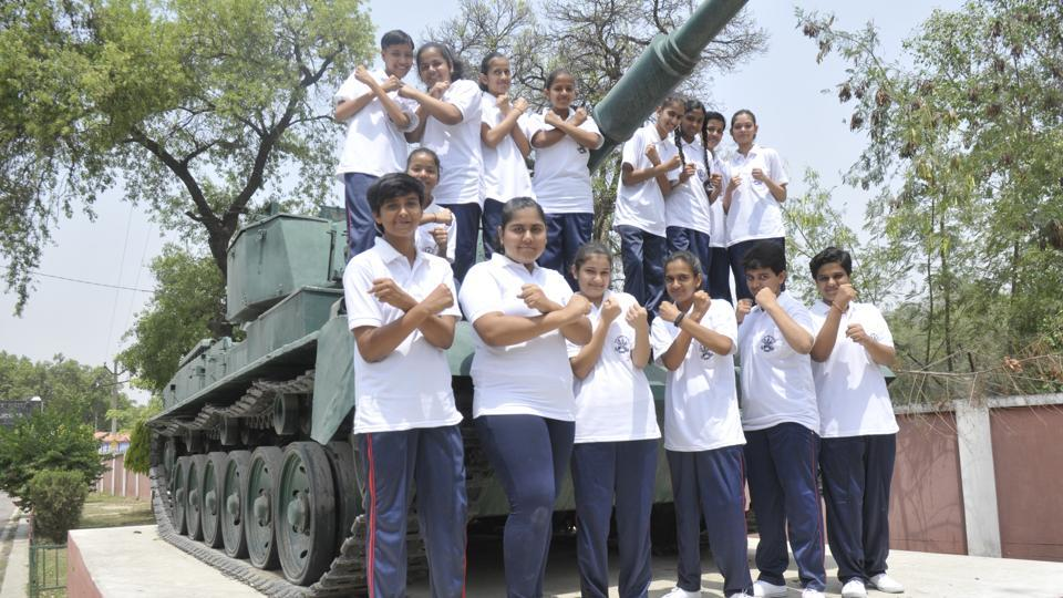 The newly admitted girls of UPSainik School in Lucknow pose before a Vijayanta tank in he school premises on Friday.