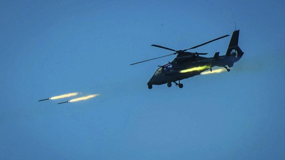 In this photo provided by China's Xinhua News Agency, a Chinese armed helicopter assaults targets with rocket projectiles in a live-fire exercise off China's southeast coast.