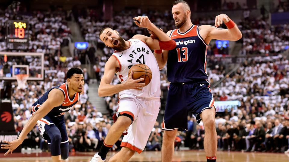 Toronto Raptors center Jonas Valanciunas (17) drives to the net past Washington Wizards centre Marcin Gortat (13) and forward Otto Porter Jr. during the first half of Game 2 of an NBA basketball first-round playoff series in Toronto, Canada on April 17, 2018. (Nathan Denette / The Canadian Press via AP)
