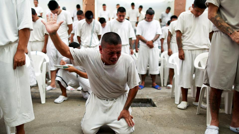 Inmates participate in a religious service at the San Francisco Gotera prison. Pastor Manuel Rivera's voice echoed through the crowded courtyard in the notorious San Francisco Gotera prison as hardened criminals wept and bowed their heads in prayer. (Jose Cabezas / REUTERS)