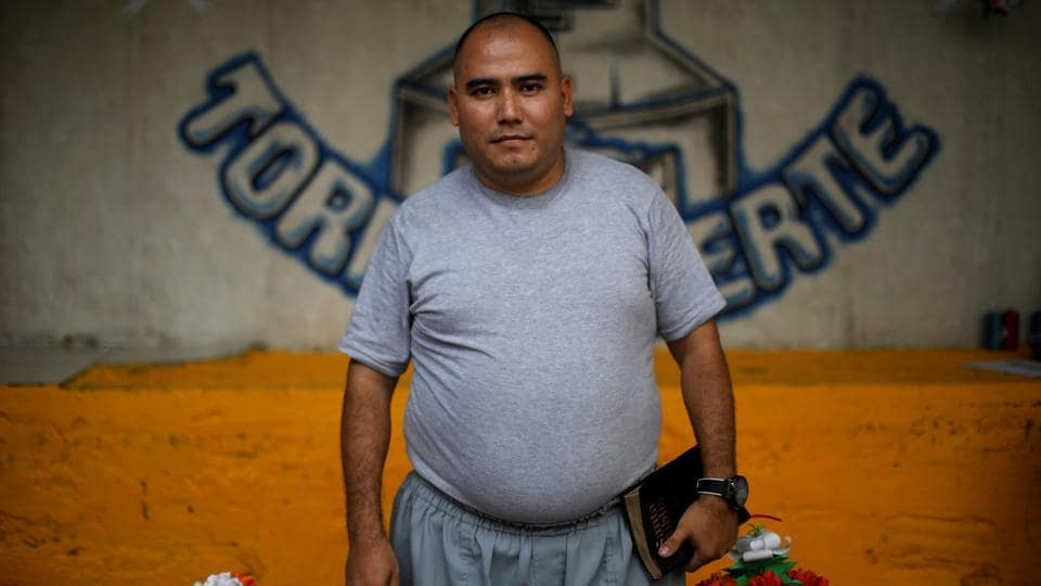 Pastor Manuel Rivera, Head of the Torre Fuerte evangelical church was a hitman for the powerful Barrio 18 gang. Now, he speaks to rows of men with spidery black tattoos on their arms, necks and faces, delivering a message of salvation: God had rescued them from violence. Returning to gang life would mean death. (Jose Cabezas / REUTERS)