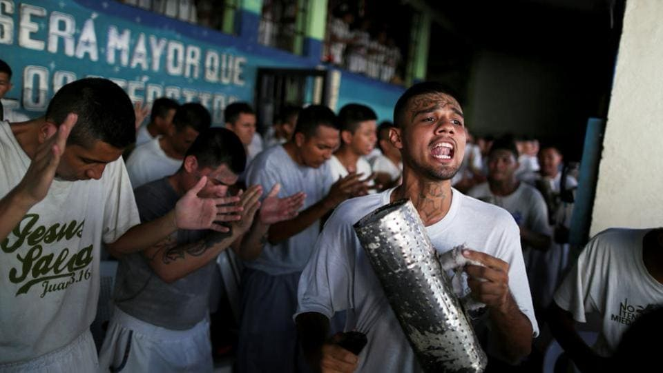 "Some wept silently while he read from a bible. Others sang hymns, clapping and waving arms enthusiastically. They chorus: ""Amen."" By embracing religion, these men can leave their gangs without retaliation, Rivera says. But if they do not show real devotion, former gang-mates may kill them, fearing they will join other gangs and become enemies. (Jose Cabezas / REUTERS)"