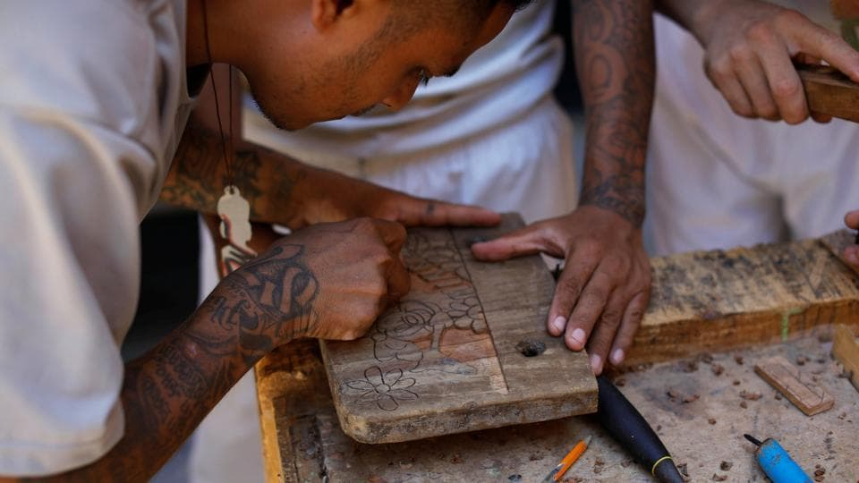 "Former members of the Barrio 18 gang take part in a carpentry workshop at the Torre Fuerte church inside the prison. ""We used to say that the gang was our family, but God took the blindfold off our eyes,"" says Rivera, 36, dressed like the other inmates in a white t-shirt, shorts and plastic sandals. (Jose Cabezas / REUTERS)"