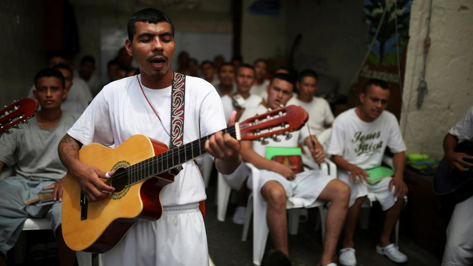 "Inside Gotera, where some inmates are serving 100-year sentences for accumulated crimes, colourful drawings of angels and prophets decorate the walls alongside biblical quotations. Inmates wearing shirts emblazoned with ""Soldier of Christ"" and ""Jesus Saved My Life"" study prayer books, weave hammocks and tend to a garden. (Jose Cabezas / REUTERS)"