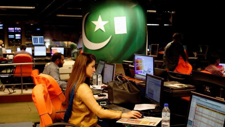 An employee works at the control room of the Geo News television channel in Karachi.