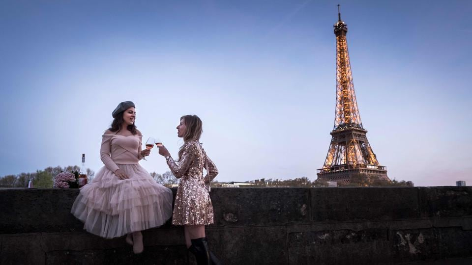 Tourists drink wine near the Eiffel tower on April 17, 2018, in Paris, France. (Lionel Bonaventure / AFP)
