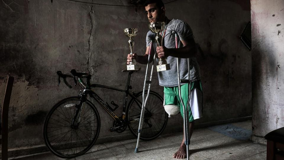 Palestinian cyclist Alaa Al-Daly, 21, who lost his leg by a bullet fired by Israeli troops along the Gaza border during a protest, stands next to his bicycle holding trophies he has won in competitions, at his home in Rafah in the southern Gaza Strip on April 19, 2018. (Said Khatib / AFP)