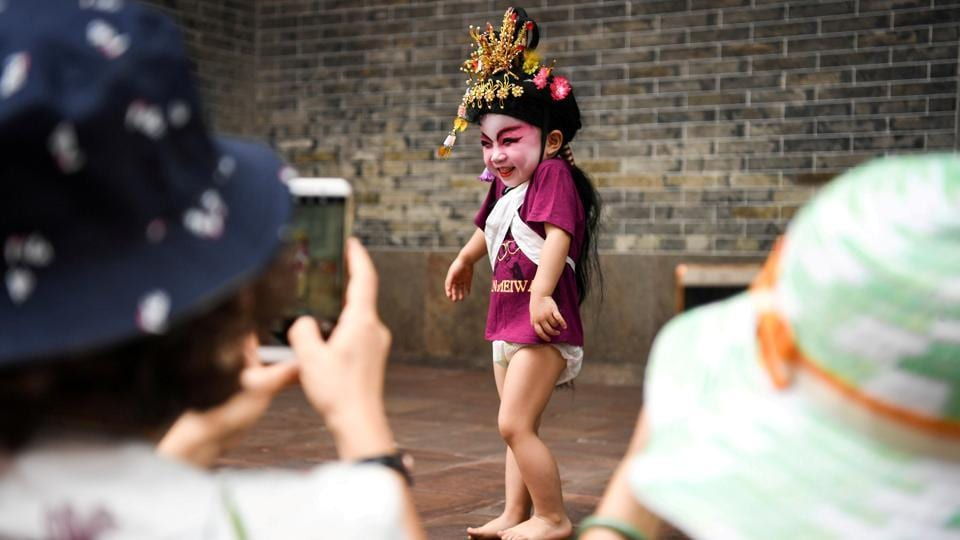 Visitors take photos of a child dressed in a traditional costume before a folk performance in Panyu, Guangdong province, China on April 18, 2018. (China Daily via REUTERS)