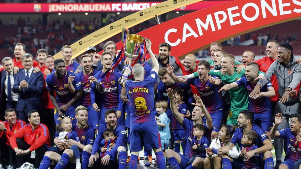 Barcelona's Andres Iniesta, center, holds up the trophy after winning the Copa del Rey final soccer match between Barcelona and Sevilla.