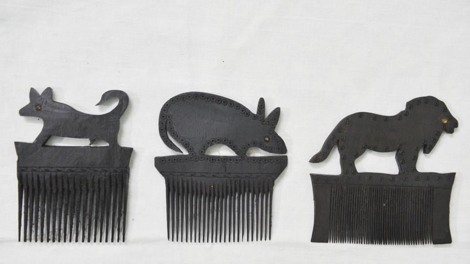 A trio of handmade wooden combs with animal motifs from Niranjan Mahawar's 1,500 specimen strong collection. All handmade and once used by a tribal man or woman somewhere in Gujarat, Rajasthan, West Bengal, Karnataka or Chhattisgarh, Mahawar's collection of combs chiselled out of buffalo horn, wood, or metal represents a wealth of cultural information about the tribes that made them. (Sanchit Khanna / HT Photo)