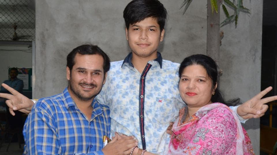 Vivek Rajput, who topped the PSEB Class 12 exams with 97.56 percent (Non-Medical stream), celebrates with his parents.  (Gurpreet Singh/HT)