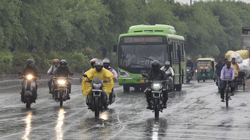 Commuters travel under light showers in New Delhi, on April 9.